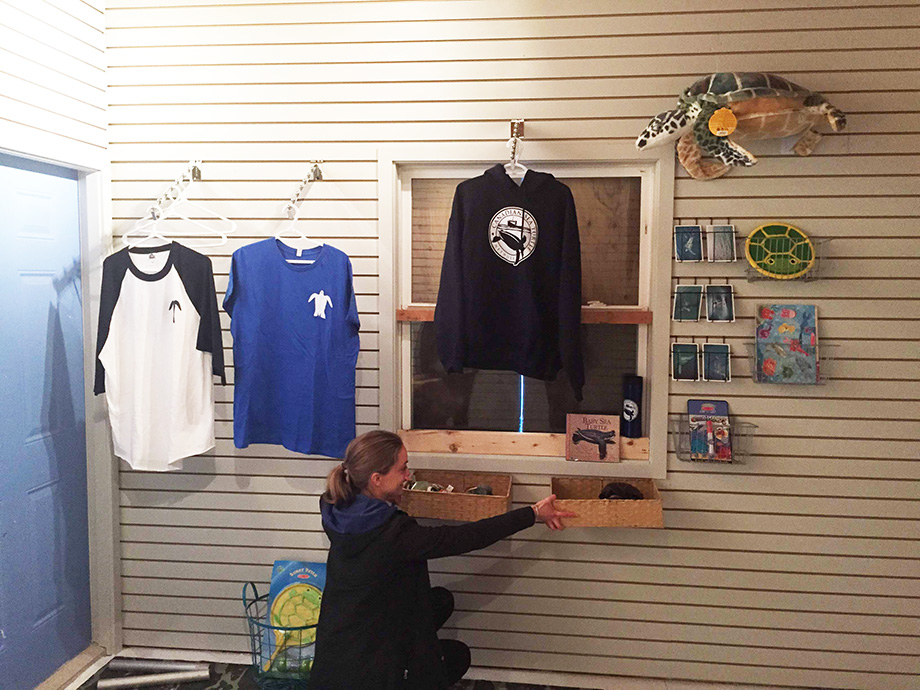 This is a photo of Kayla helping figure out how to set up our sales display. Kayla has been an amazing project manager for the Sea Turtle Centre--an impressive feat particularly because of the number of moving parts to this adventure. As you can see we are selling a few things at the Centre. 100% of our profits are used to help fund our research and community outreach programs.